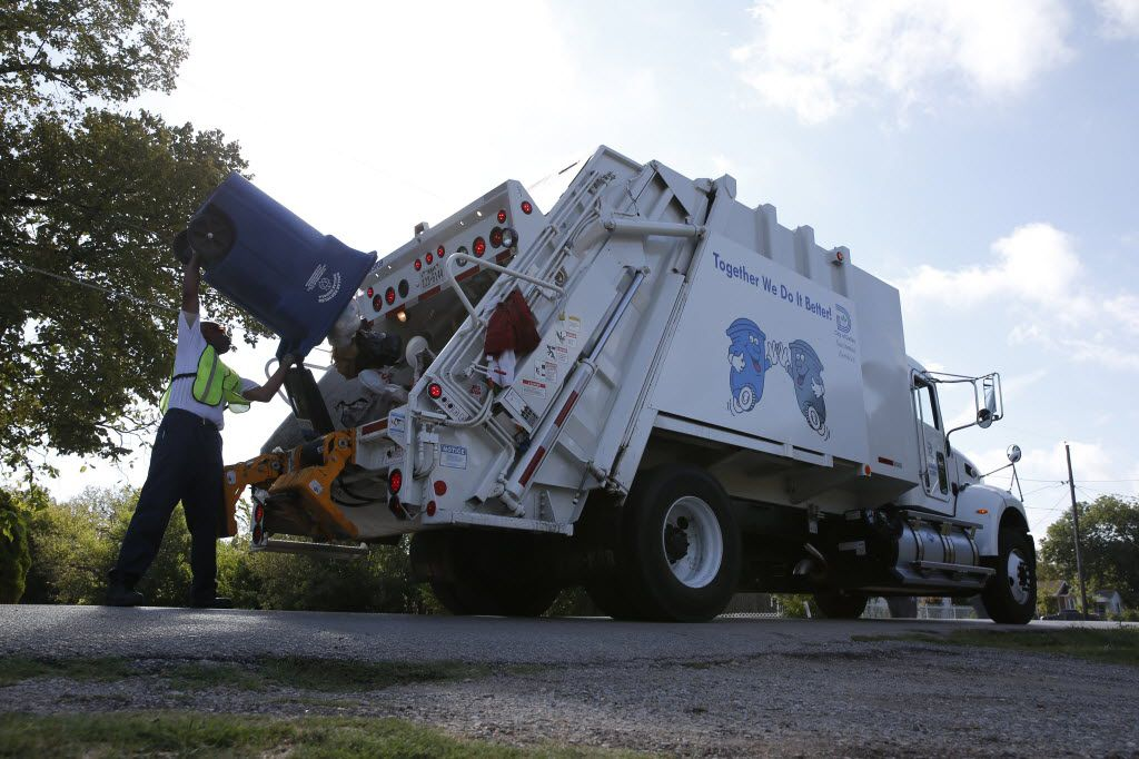 Darrell Kennedy unloads a recycling bin for the city of Dallas in a South Dallas neighborhood. (2015 File Photo/Nathan Hunsinger)
