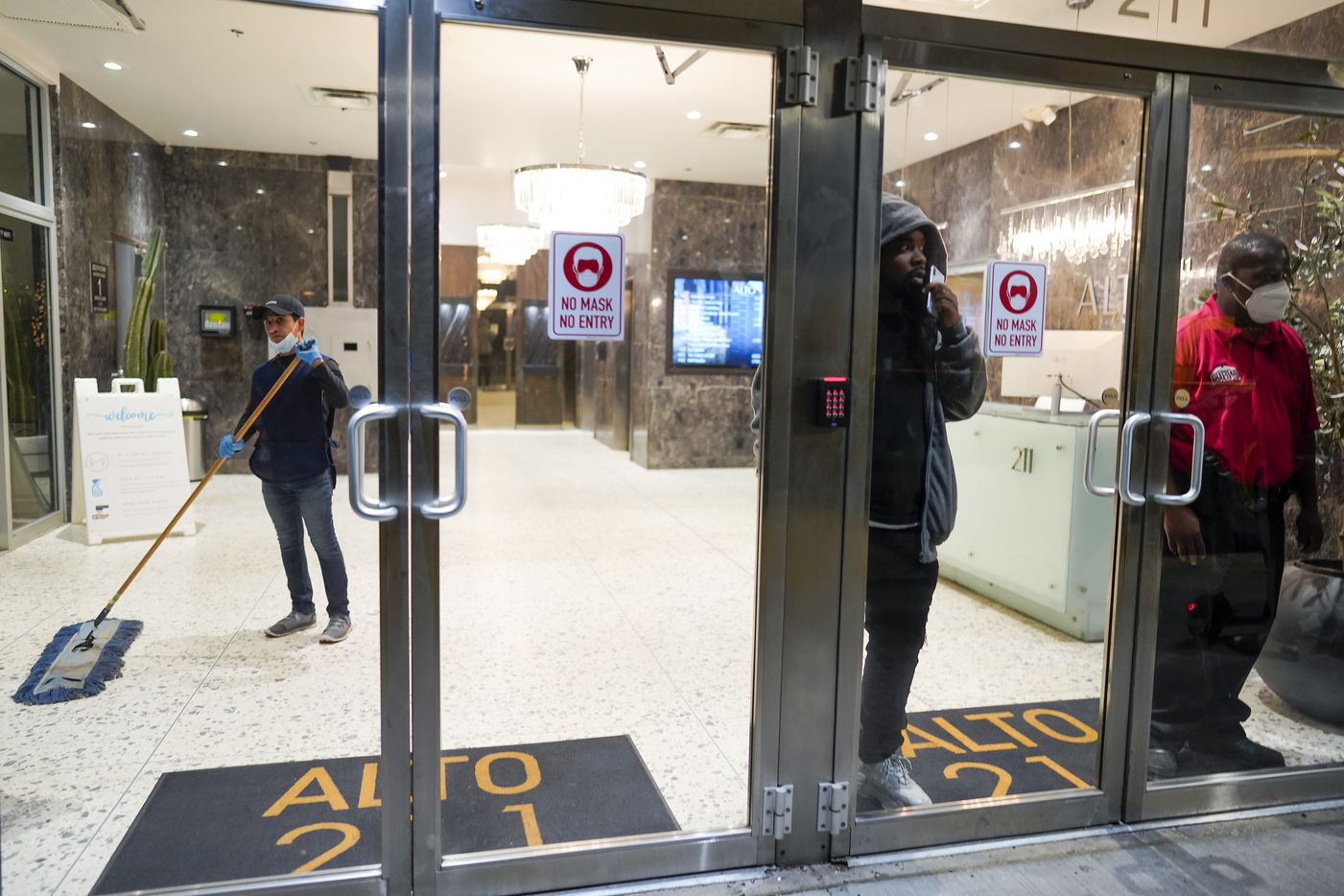People watch through the doors of Alto 211 on Ervay Street as demonstrators in downtown Dallas after a Kentucky grand jury brought no charges against Louisville police for the killing of Breonna Taylor on Wednesday, Sept. 23, 2020.