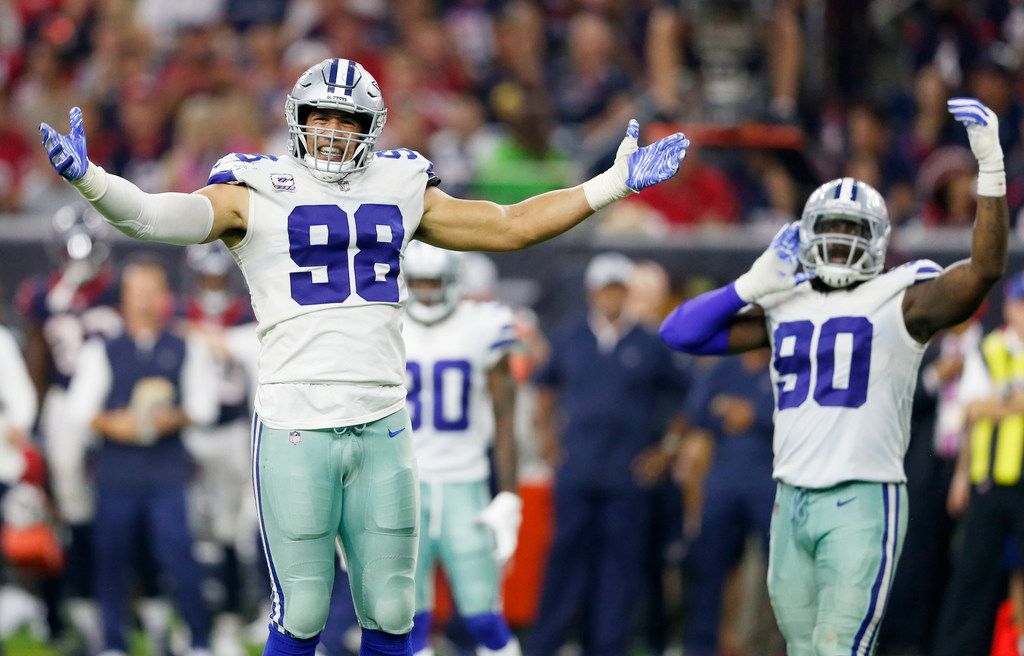Dallas Cowboys defensive end Tyrone Crawford (98) and Dallas Cowboys defensive end Demarcus Lawrence (90) get the crowd riled up before a play during the second half of play at NRG Stadium in Houston on Sunday, October 7, 2018. Houston Texans defeated Dallas Cowboys 19-16 in overtime. (Vernon Bryant/The Dallas Morning News)
