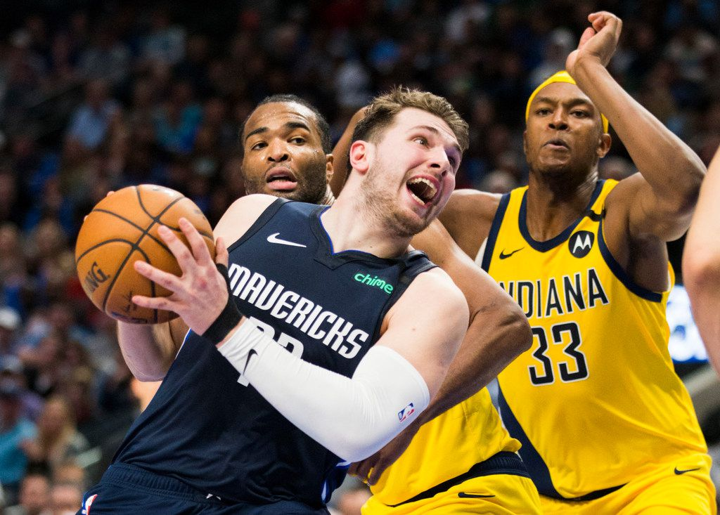 Dallas Mavericks guard Luka Doncic (77) is fouled by Indiana Pacers forward T.J. Warren (1) with center Myles Turner (33) during the fourth quarter of an NBA game between the Indiana Pacers and the Dallas Mavericks on Sunday, March 8, 2020 at American Airlines Center in Dallas. (Ashley Landis/The Dallas Morning News)
