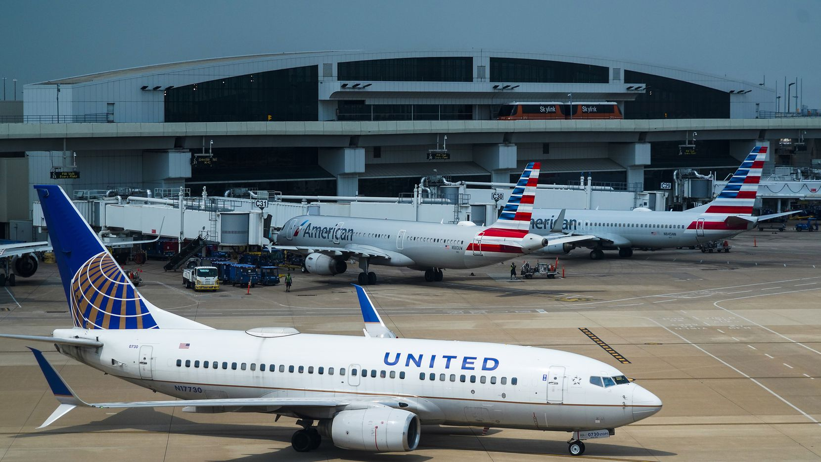 A United Airlines plane pushes away from a gate at Terminal E as American Airlines planes are seen at Terminal C on Sept. 8 at DFW Airport.