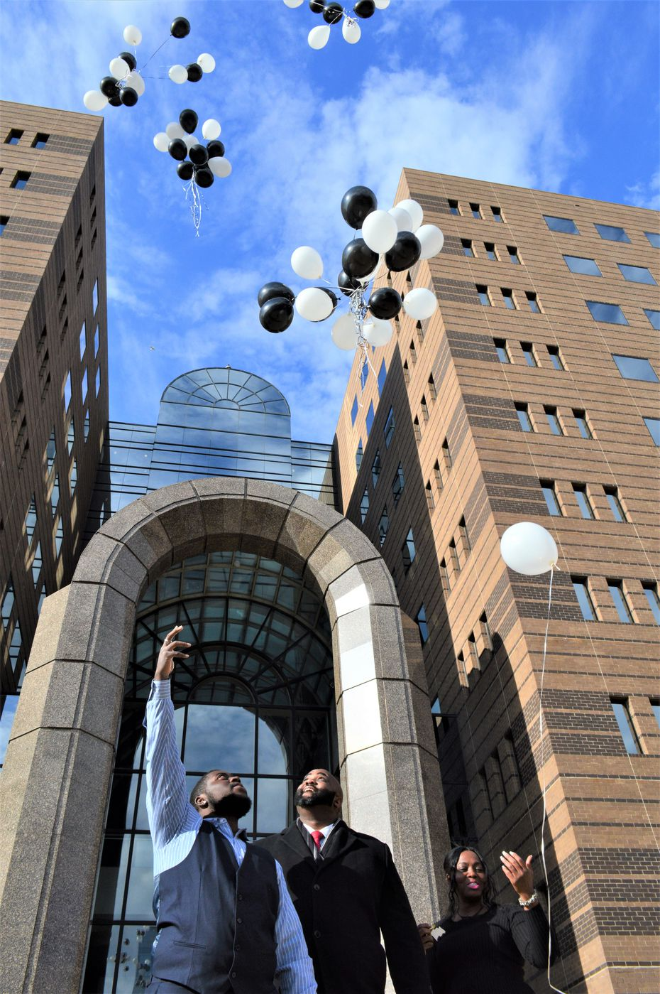 In November, Sammie Anderson (right) launched balloons with her family outside a Dallas courthouse to celebrate the exoneration of her sons Grant Bible (left) and Sam Bible, who is not pictured, for allegedly interfering with DeSoto police last August. The family's attorney Anthony Farmer (center) also joined in the celebration.