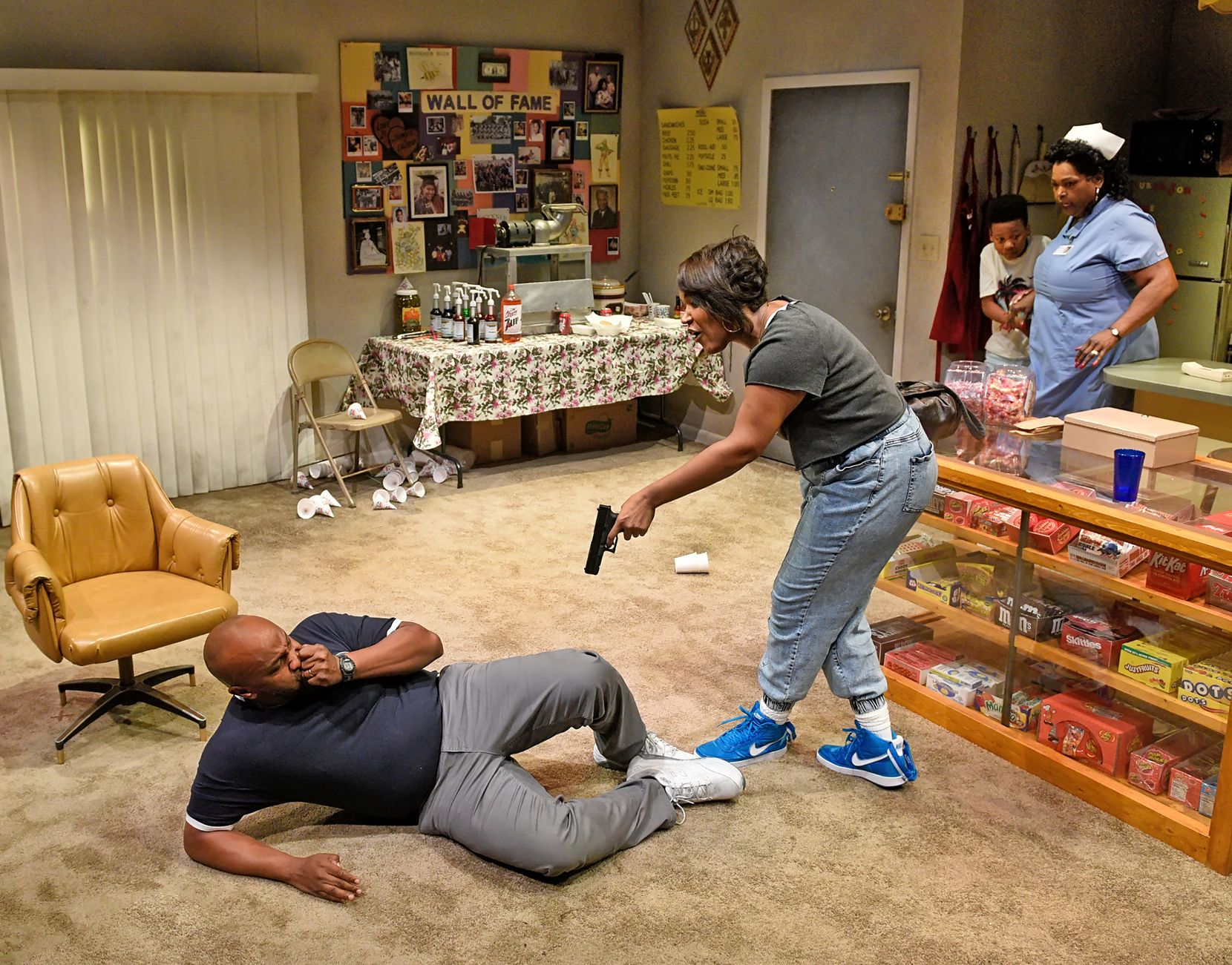 Rose (Claudia Logan, center) threatens neighbor Donnie (Jamal Sterling) as Jon-Jon (Esau Price) and Laura Mae (Liz Mikel) watch from the kitchen in Penny Candy.