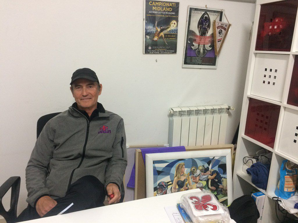 Art Briles poses at his desk in a cramped office.