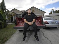 Brandon Gonzales sits on the back of his step-father's truck outside his mother's home in Poinciana, Fla.