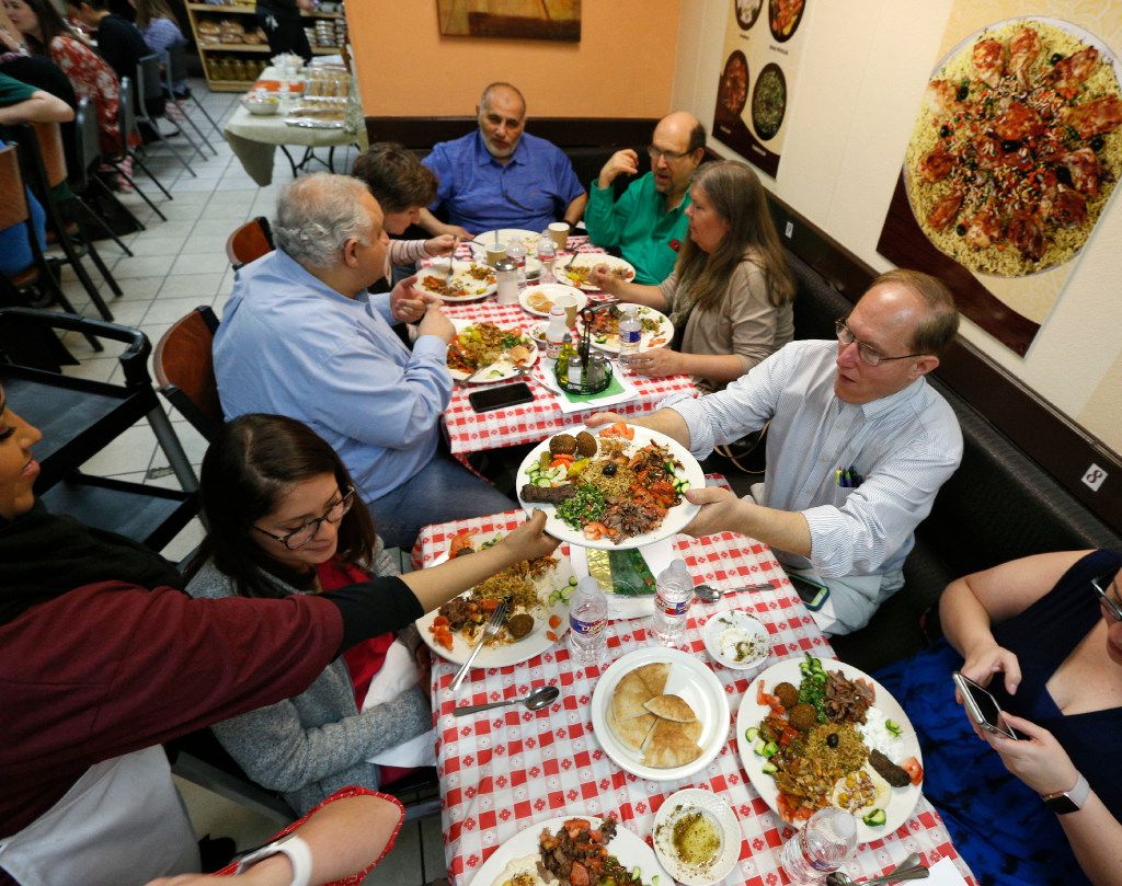 John Allums grabs a plate of Iraqi food during the 'Breaking Bread' cultural exchange dining event at Bilad Bakery & Restaurant in Richardson, Texas on March 8, 2017. (Nathan Hunsinger/The Dallas Morning News)