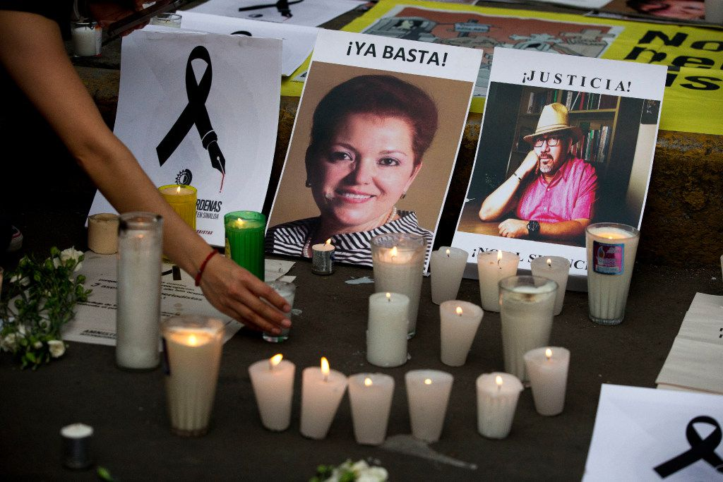 A candle is placed in front of pictures of murdered journalists Miroslava Breach (left) and Javier Valdez during a demonstration against the killing of journalists outside the Interior Ministry in Mexico City. Valdez's killing spurred an outcry unseen previously during the tragically frequent murders of Mexican journalists. It has drawn together competing outlets, as well as foreign governments, the international press and human rights organizations in broad condemnation.