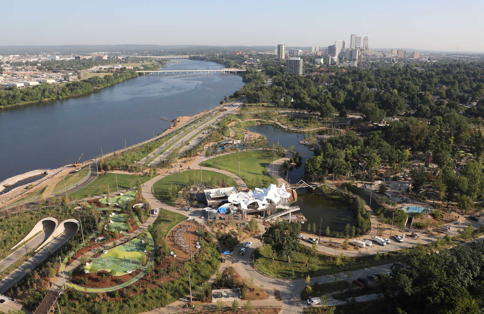 This 2018 aerial photo of Gathering Place, which runs along the Arkansas River, shows the Tulsa skyline in the background.