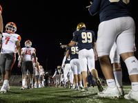 Rockwall and Jesuit players stay five yards apart instead of shaking hands, due to coronavirus concerns, after playing each other in a high school football game on Friday, October 2, 2020 at Postell Stadium in Dallas. Rockwall won 60-38.
