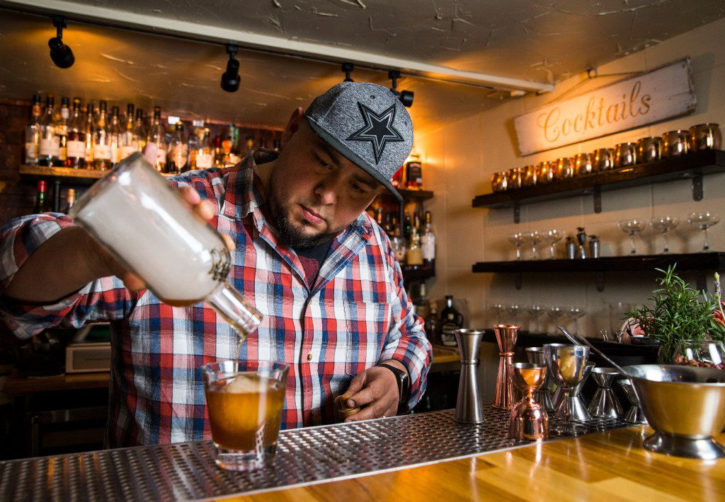 Mixologist Manny Casas pours the smoke-infused cocktail into a glass with ice.
