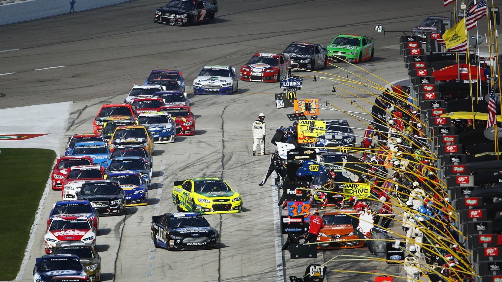 NASCAR Sprint Cup Series pull into their pits for a four-tire change during the first pit stop in the AAA 500 at the Texas Motor Speedway in Fort Worth, Sunday, November 3, 2013.