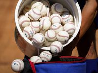 A Texas Rangers player dumps a bucket of baseballs from infield practice into a bag during a spring training workout at the team's training facility on Thursday, Feb. 13, 2020, in Surprise, Ariz.