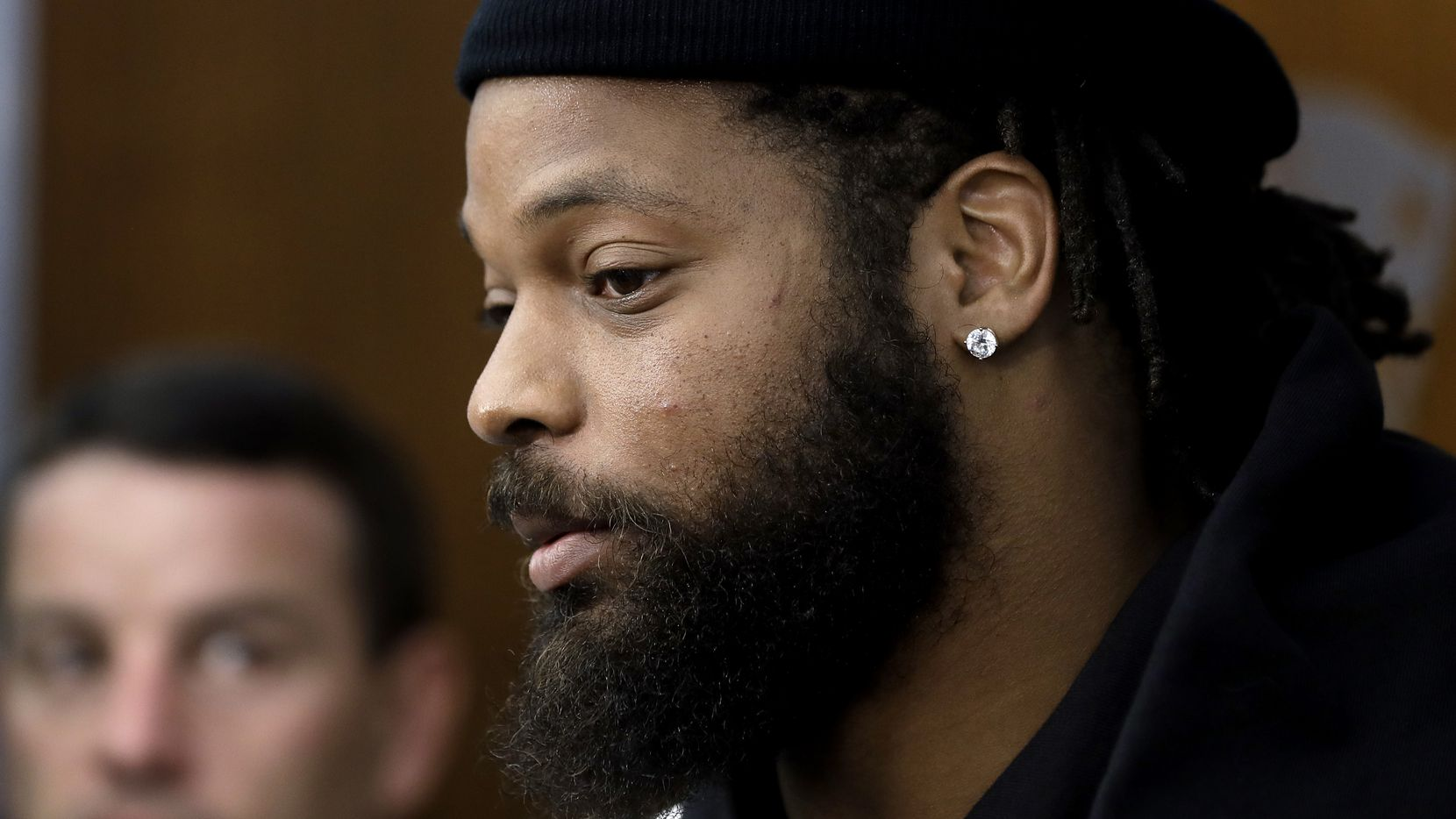 New England Patriots defensive lineman Michael Bennett speaks with members of the media in the team's locker room following an NFL football practice, Wednesday, Oct. 23, 2019, in Foxborough, Mass. (AP Photo/Steven Senne)
