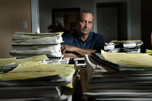 Former Dallas firefighter Joe Bob Betzel is surrounded in his Midlothian home by paperwork filed in a pay raise dispute with the city. (2006 File Photo/Staff)