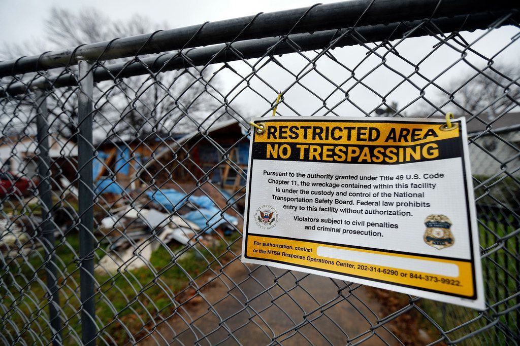 """An NTSB """"No Trespassing"""" sign hangs on a chain link fence surrounding a wrecked home in the 3500 block of Espanola Drive."""