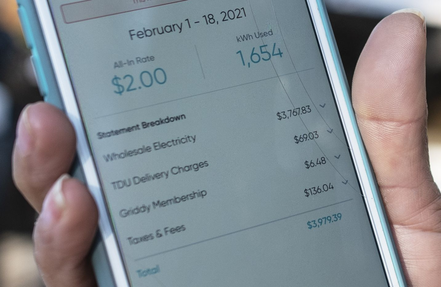 Ivet Cantu, 45, shows her electricity bill from Griddy energy on an app totaling $3,979.39 after additional charges and fees, outside of her home in Dallas, on Friday, Feb. 19, 2021.