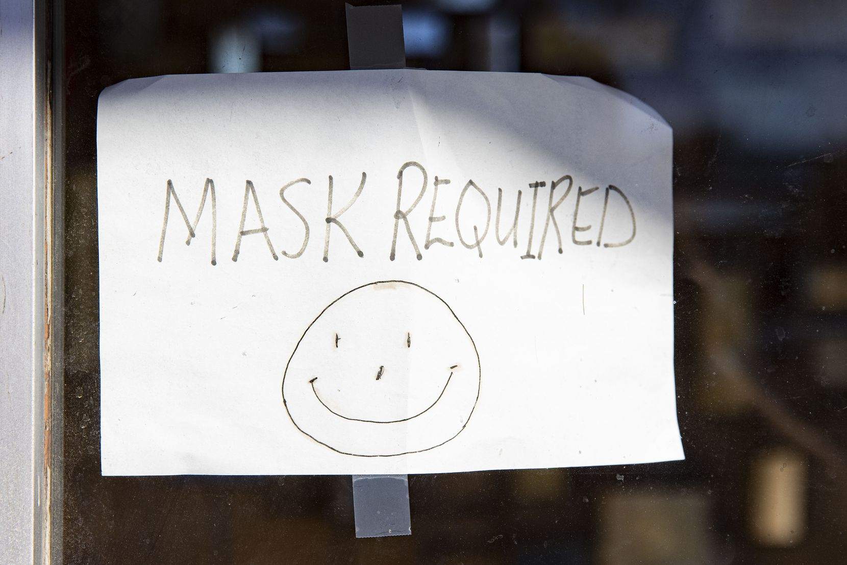 A hand drawn mask required sign at Oliver's Hair Replacements on Greenville Ave. in Dallas on Tuesday, March 2, 2021. Gov. Greg Abbott announced that all business can reopen at 100 percent capacity and also ended the mask mandate starting next week. (Juan Figueroa/ The Dallas Morning News)