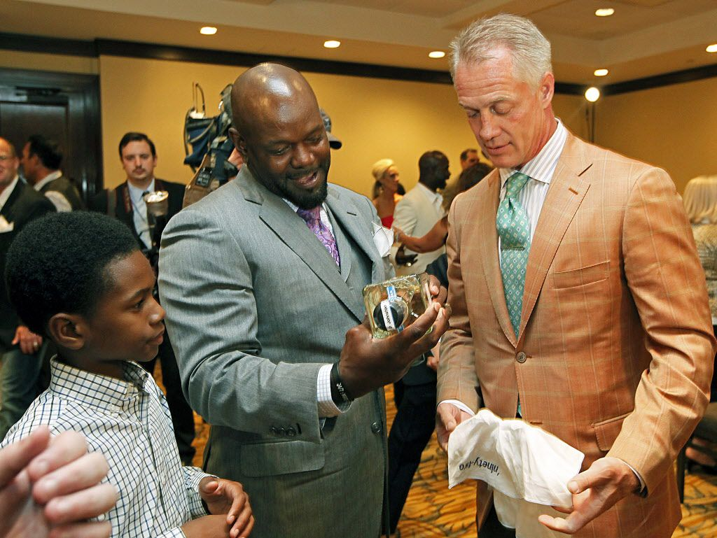 Emmitt Smith (center) stands with his son, Emmitt IV, as he displays a gift bottle of tequila to his former team mate, Daryl Johnston (right) as members of the Super Bowl Championship teams of the Dallas Cowboys gathered at the Westin Stonebriar Resort in Frisco on Friday night, May 11, 2012 for the friday night dinner prior to the Emmitt Smith Celebrity Invitational Golf Tournament. (Stewart F. House/Special Contributor)
