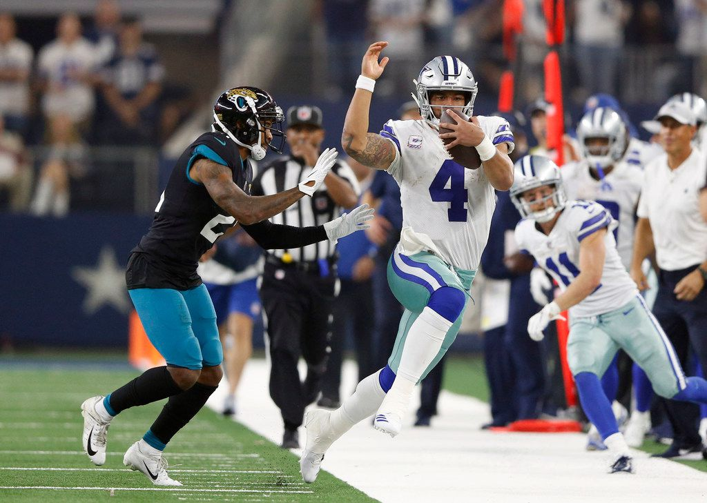 Dallas Cowboys quarterback Dak Prescott (4) rushes up the field for a long run as he is forced out of bounds by Jacksonville Jaguars cornerback A.J. Bouye (21) during the second half of play at AT&T Stadium in Arlington, Texas on Sunday, October 14, 2018. Dallas Cowboys defeated the Jacksonville Jaguars 40-7. (Vernon Bryant/The Dallas Morning News)