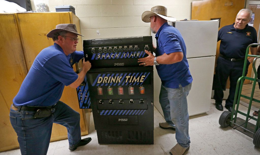 Patrick Travers (left) and Kelly Walker (center) install a drink machine stocked with soft drinks as Capt. Jeff Modawell looks on in the hallway at Station 53 in Dallas, Wednesday, July 12, 2017.  (Jae S. Lee/The Dallas Morning News)