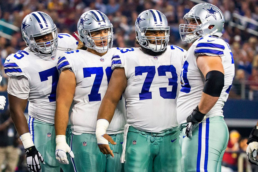 Dallas Cowboys offensive tackle Cameron Fleming (75), offensive guard Xavier Su'a-Filo (76), and center Joe Looney (73) look to offensive guard Zack Martin (70) as they huddle during the first half of an NFL football game against the Washington Redskins at AT&T Stadium on Thursday, Nov. 22, 2018, in Arlington.