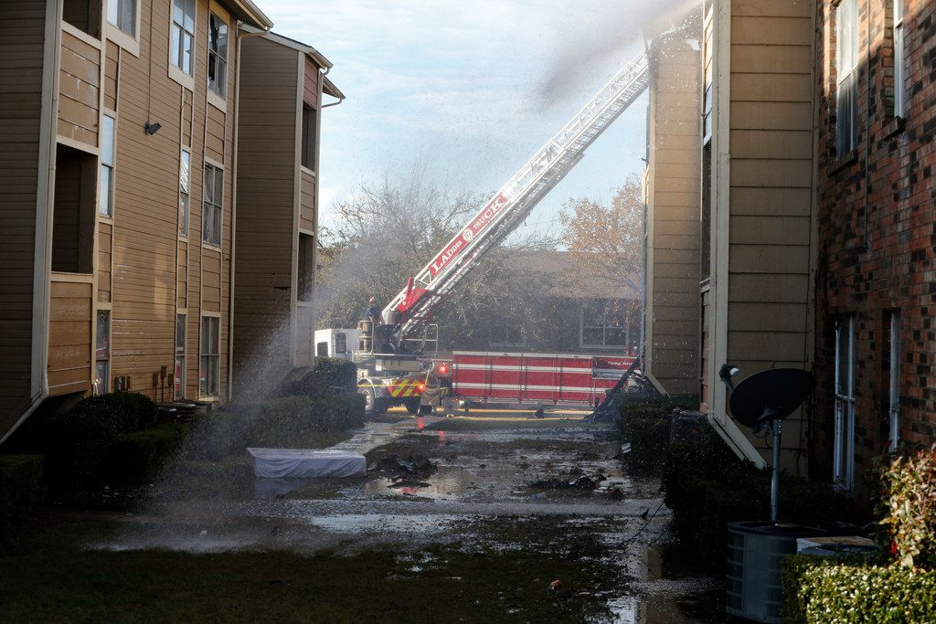 Firefighters put out hot spots on Nov. 21, 2018 during an apartment fire at the Meadows at Ferguson, located at the intersection of I- 635 and Ferguson Road.