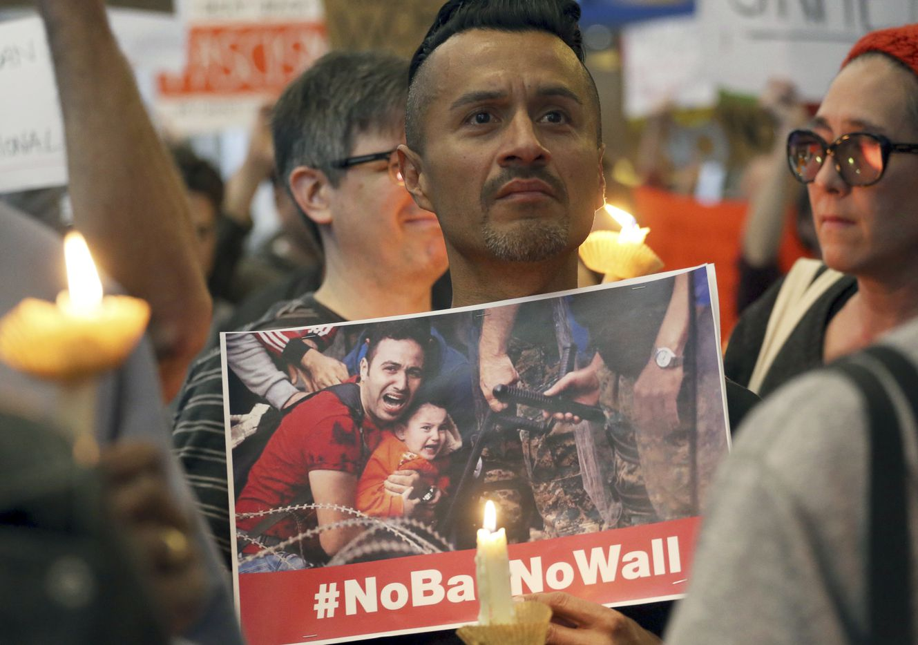 A man joins hundreds of demonstrators opposed to President Donald Trump's executive order barring entry to the U.S. by Muslims from certain countries at the Tom Bradley International Terminal at Los Angeles International Airport Saturday, Jan. 28, 2017, in Los Angeles.