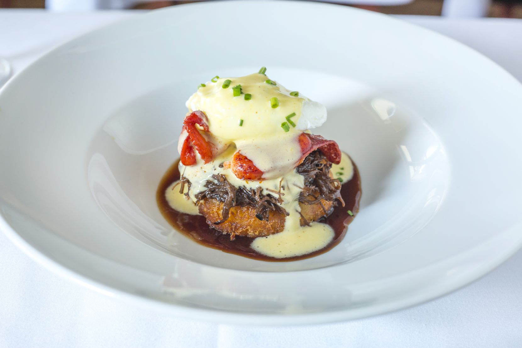 Ocean Prime's Father's Day menu includes braised short rib surf and turf with a lobster claw, poached egg, hollandaise and crispy gouda potato cake.