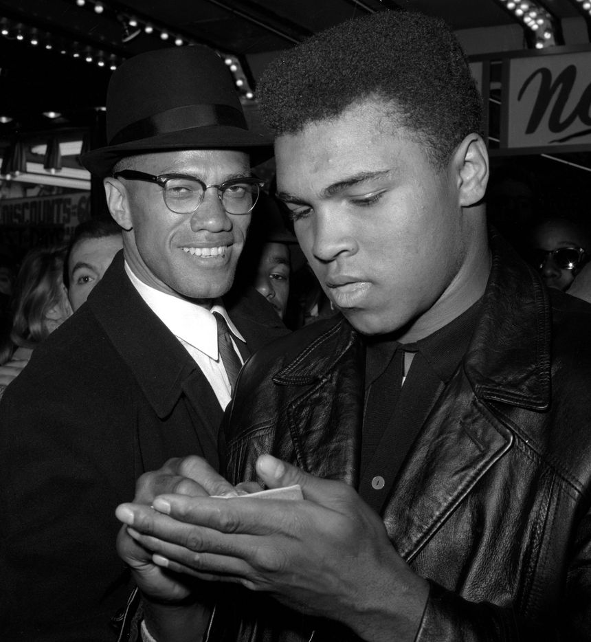 In this March 1, 1964, file photo, world heavyweight boxing champion, Muhammad Ali, right, is shown with Black Muslim Leader, Malcolm X, outside the Trans-Lux Newsreel Theater  in New York City, after watching a screening of films on Ali's title fight with Sonny Liston in Miami Beach.
