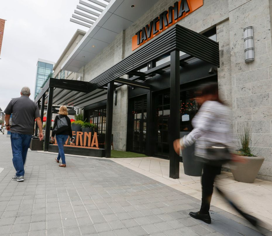 Pedestrians walk past of Taverna Thursday, November 16, 2017, in the Plano, Texas' Legacy West development. The restaurant is owned by Lombardi's Inc., which is suing its insurer over a denial of its business interruption insurance claim.