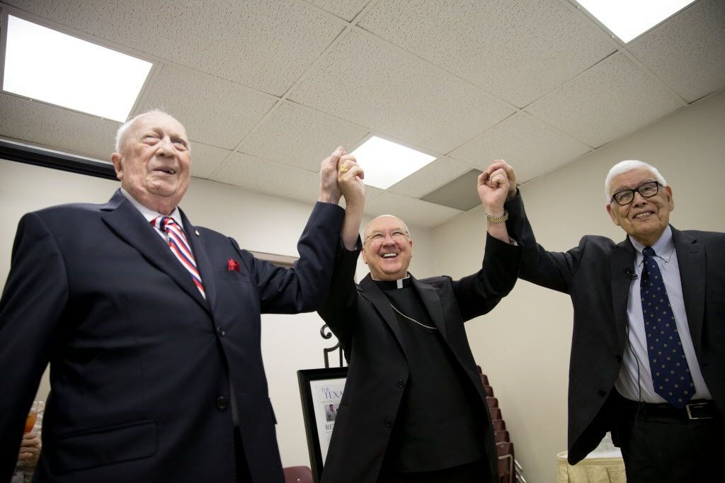 Steven Landregan (left) and Tony Ramirez raise their arms holding hands with Bishop Kevin J. Farrell in celebration during the retirement party for Landregan and Ramirez at the Diocese of Dallas Pastoral Center on June 23, 2016.