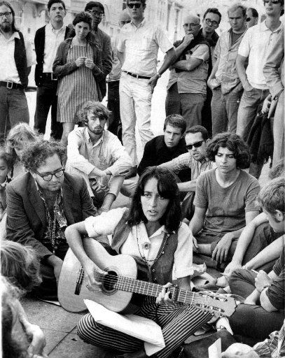 Folk singer Joan Baez sits at the corner of Haight and Ashbury in San Francisco, serenading hippies and tourists in this file photo taken Friday, Sept. 22, 1967.