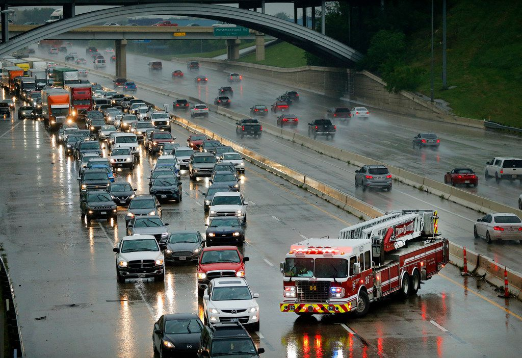 A Dallas Fire Department truck blocks lanes of traffic after an 18-wheeler jackknifed on eastbound Interstate 30 near Hampton Road in Dallas on April 24, 2019.