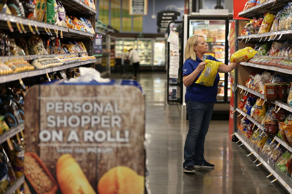 Diana Lynch, a ClickList associate, grabs chips off a shelf to fulfill an online order at the Kroger Marketplace in Midlothian.