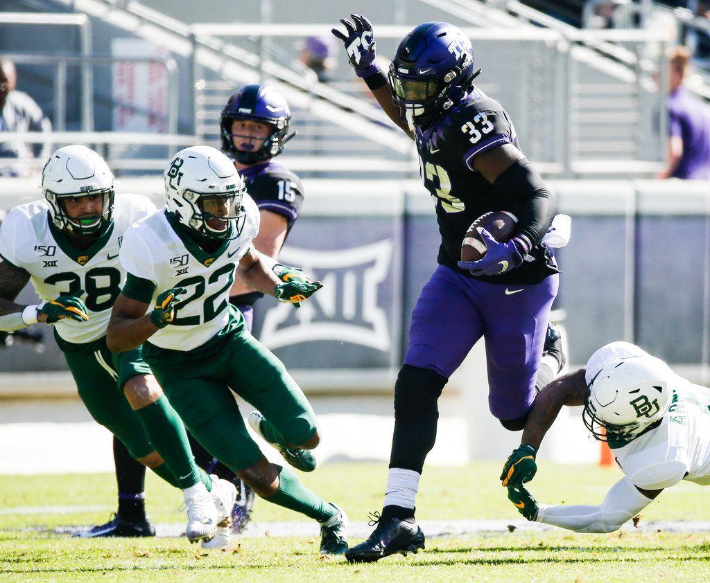 TCU Horned Frogs running back Sewo Olonilua (33) runs a lane past Baylor Bears linebacker Jordan Williams (38), safety JT Woods (22), and cornerback Grayland Arnold (1)  during the first half of an NCAA football matchup between the Texas Christian University Horned Frogs and the Baylor Bears at Amon G. Carter Stadium in Fort Worth, Texas, on Saturday, No. 9, 2019.
