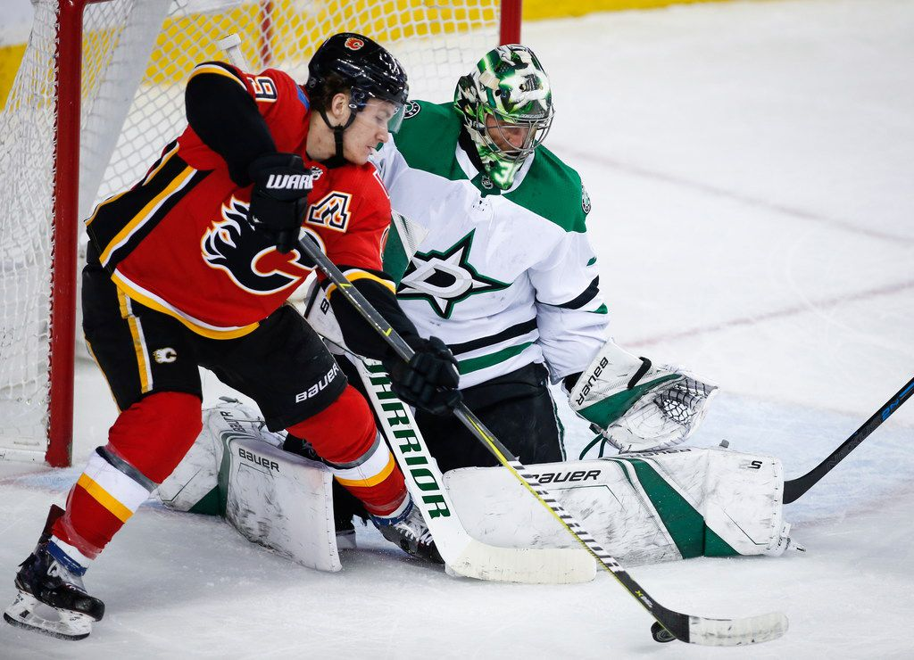 Dallas Stars goalie Ben Bishop, right, blocks the net on Calgary Flames' Matthew Tkachuk during the first period of an NHL hockey game Wednesday, March 27, 2019, in Calgary, Alberta. (Jeff McIntosh/The Canadian Press via AP)