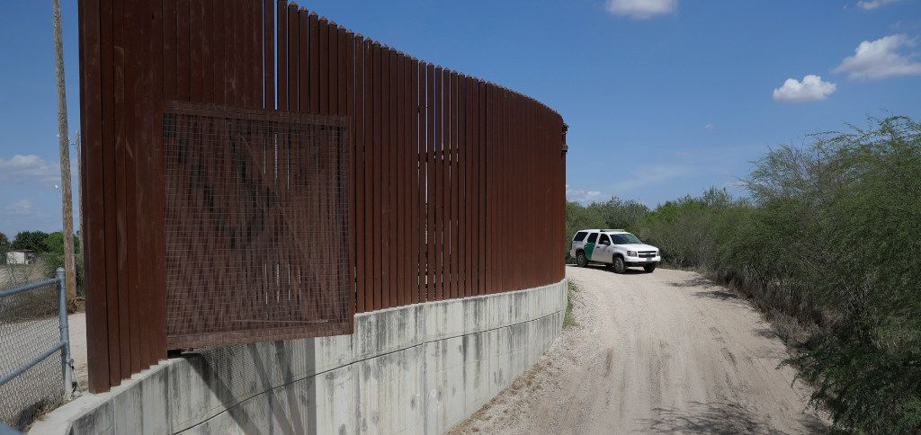 A U.S. Customs and Border Patrol agent passes along a section of border levee wall in Hidalgo.