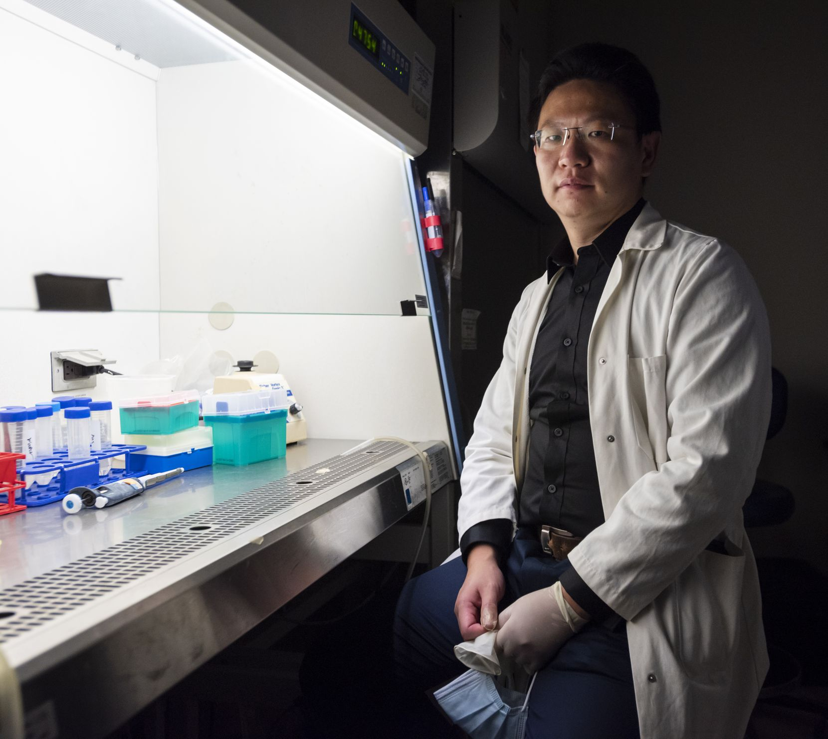 Dr. Zhihao Wu of Southern Methodist University sits next to a biosafety cabinet inside a campus lab.
