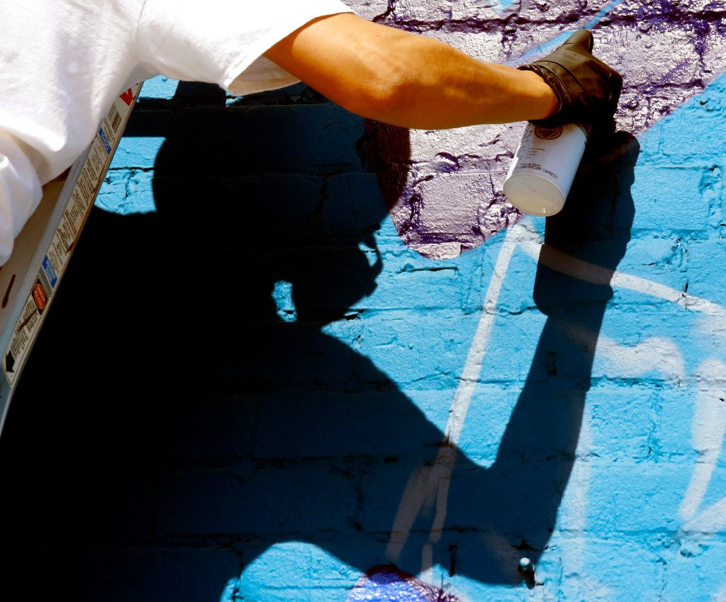 """Dallas-based muralist Isaac """"IZK"""" Davies' shadow shows the mask he wears to prevent him from inhaling the fumes from a can of spray paint as he works on a mural of the famous Nolan Ryan punch scene on the Crowdus Street side of Wits End in Deep Ellum. The mural was commissioned to promote DJ Edgar Blue No Request Served Sunday's roof top party at the Wits End. (Ron Baselice/ The Dallas Morning News)"""