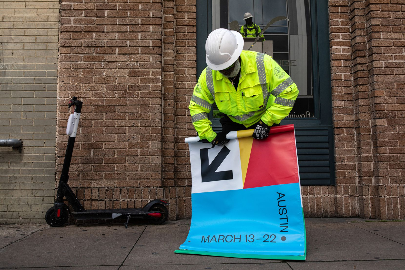 Joseph Alberts rolls up a South by Southwest banner after it was removed from a lamp post in downtown Austin. The 2020 edition of SXSW was canceled in March over coronavirus concerns.
