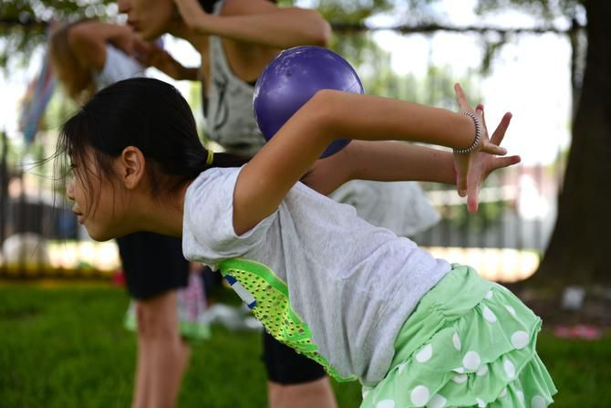 Vika Yun, 8, rolls a ball down her back during summer camp at River of Life.