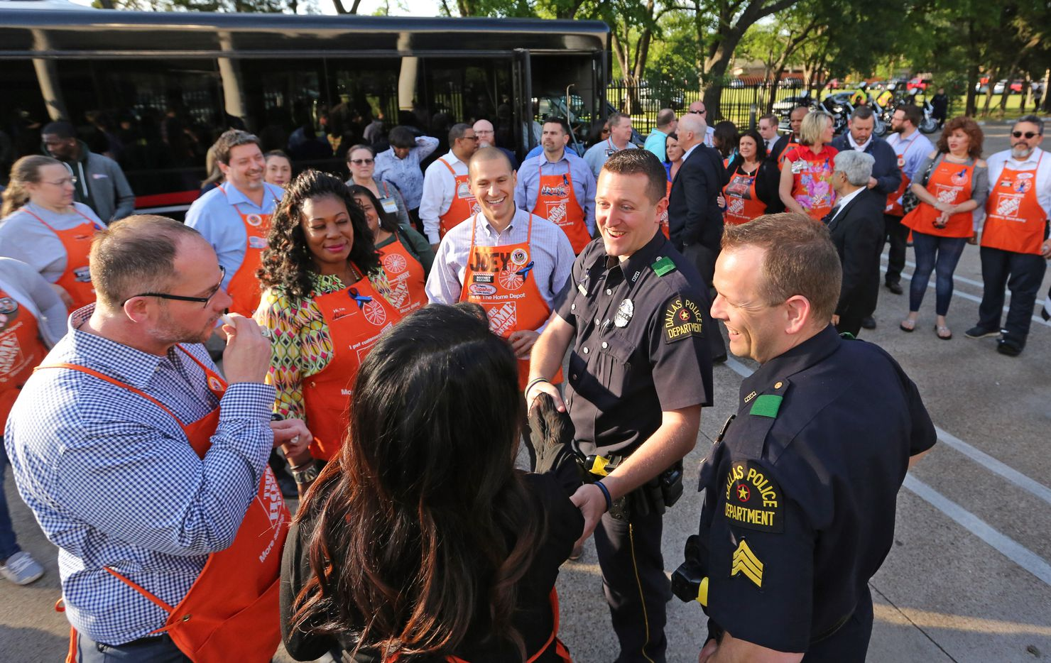 Neighborhood Police Officer Kevin Kelley greats a busload of Home Depot employees at a candlelight vigil to support Dallas Police Officer Crystal Almeida, and to honor the memory of Officer Rogelio Santander, Jr., held at the Dallas Police Northeast Division substation on Thursday, April 26, 2018.