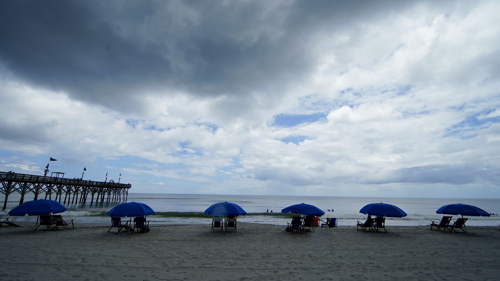 Beach umbrellas are separated on the sand Thursday, July 9, 2020, in Myrtle Beach, S.C. (AP Photo/Chris Carlson)