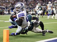 El corredor de los Cowboys de Dallas, Ezekiel Elliott (izq), es tacleado antes de cruzar la zona de anotación en el juego contra los Eagles de Filadelfia, el 27 de septiembre de 2021 en el At&T Stadium de Arlington.