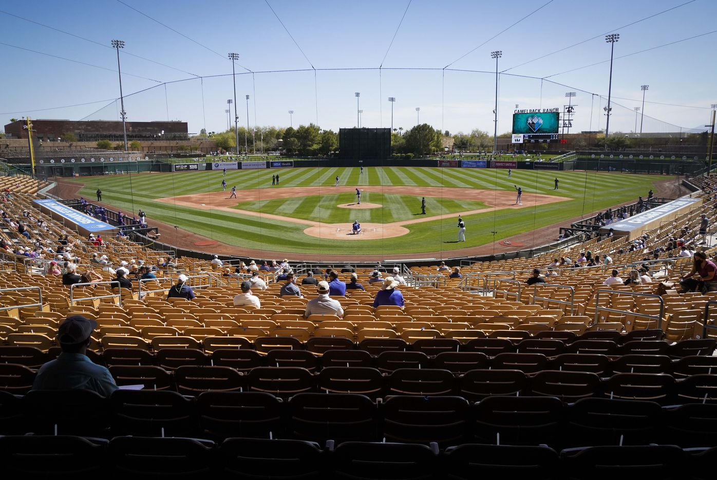 Socially distant fans watch as Chicago White Sox shortstop Tim Anderson steps into the batters box to face Texas Rangers pitcher Kohei Arihara during the first inning of a spring training game at Camelback Ranch on Tuesday, March 2, 2021, in Phoenix, Ariz.