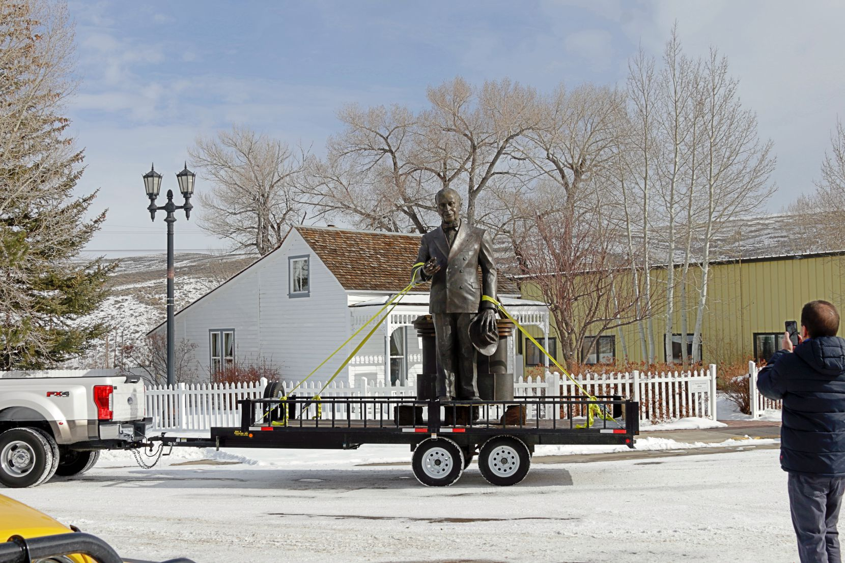 James Cash Penney statue on a trailer drives past the home where Penney lived when he opened his first store. Penney's house is now a museum.