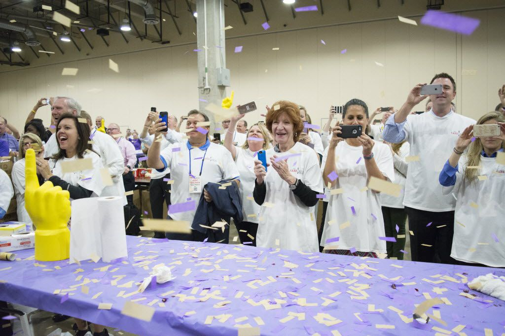 Spread the Love volunteers cheer and take videos shortly after finding out that they broke the Guinness World Record for the highest number of PB&J sandwiches made in one room in one hour.
