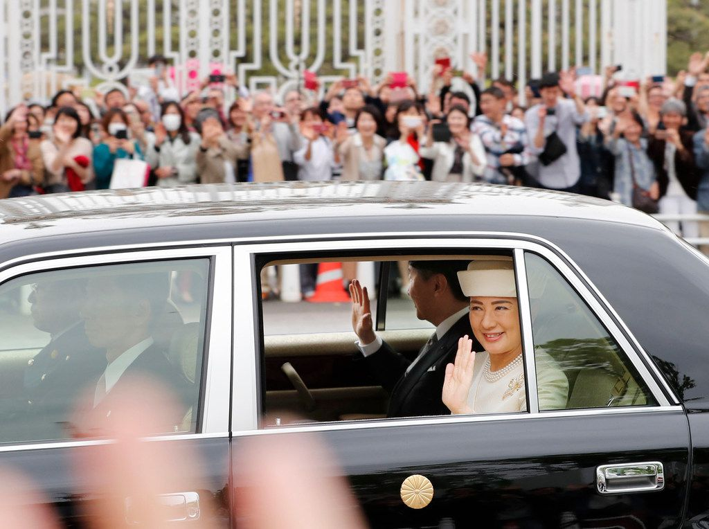 People gather as the car carrying new Emperor Naruhito and Empress Masako passes near state guest house in Tokyo on May 1, 2019. Naruhito inherited the sacred sword and jewel that signaled his succession and pledged in his first public address to follow his father's example by devoting himself to peace and sharing the people's joys and sorrows.