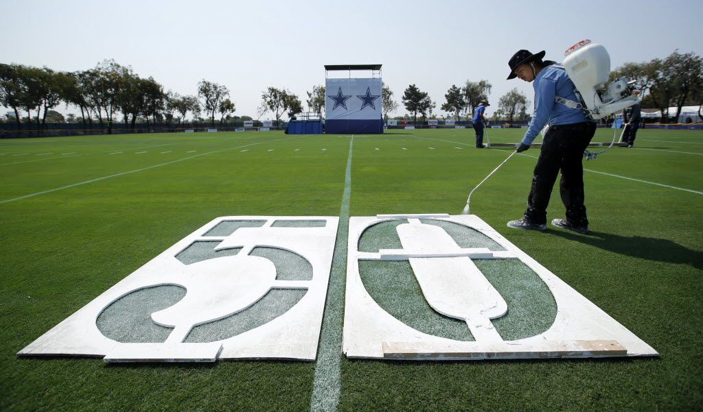 Robert Vega of Oxnard City Corps spray paints the 50 yard line markers on a practice field in preparation for tomorrow's start of Dallas Cowboys training camp in Oxnard, California, Friday, July 29, 2016. (Tom Fox/The Dallas Morning News)