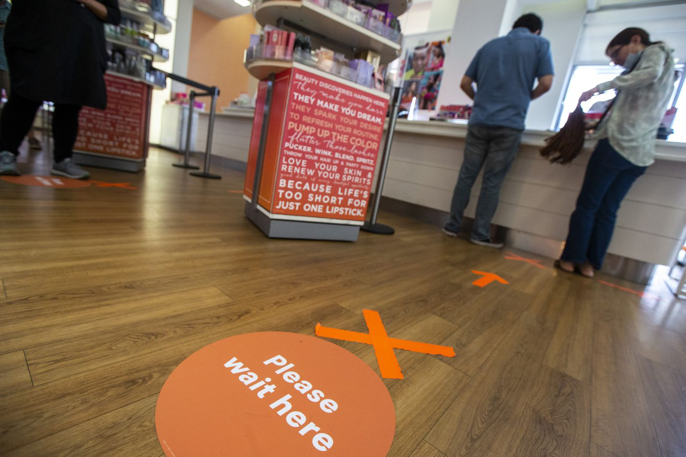 Social distancing markers are taped to the ground as customers check out at the registers at the Ulta Beauty store at The Shops at Park Lane in Dallas.